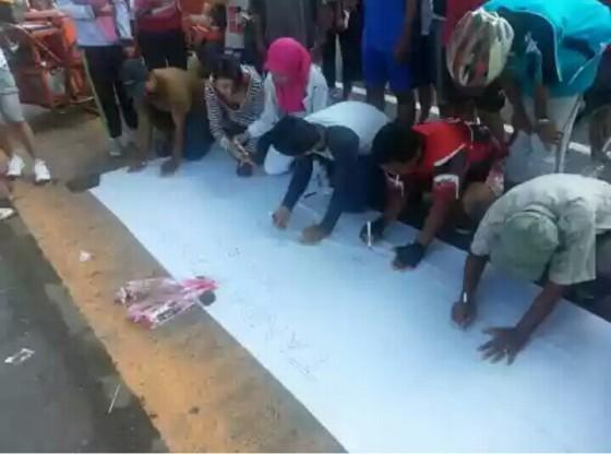 Warga Surabaya menandatangani selembar kain putih sebagai bentuk dukungan pada Ibu Risma untuk tetap menjadi Walikota Surabaya (foto by Pratama W Budiarta)