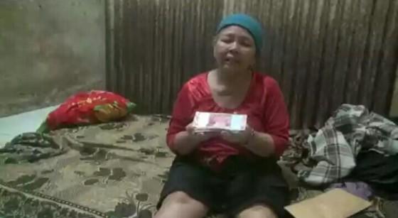 Saeni, ibu penjual nasi di kawasan Pasar Induk Rao Kota Serang, yang jualannya disita Satpol PP Kota Serang, menunjukkan uang bantuan dari Presiden Joko Widodo, Ahad siang. TEMPO/Darma Wijaya