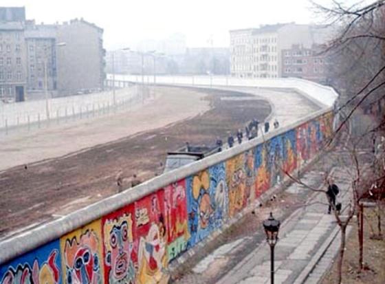 """Pemandangan dari sisi Berlin Barat (temboknya penuh dengan lukisan) pada tahun 1986. Kawasan """"daerah terlarang"""" berada di sisi timur tembok ini, mengikuti bentuk dari Kanal Luisenstadt. (Wikipedia)"""